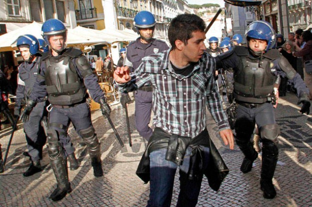 A protester runs away from riot policemen during a charge in Lisbon downtown during the Portuguese general strike